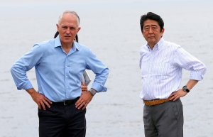 Japanese PM Abe and Australian PM Turnbull walk together along forehsore of Sydney Harbour in Sydney, Australia
